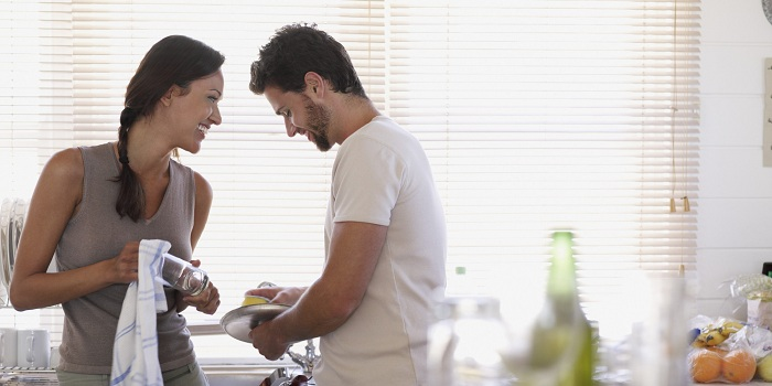 Couple washing up in kitchen, woman smiling at man