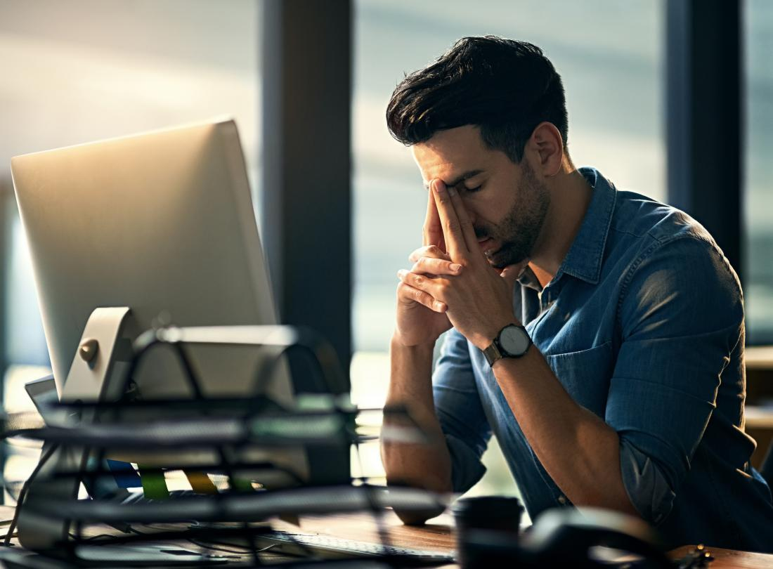 man-sitting-at-desk-at-work-stressed-and-tired