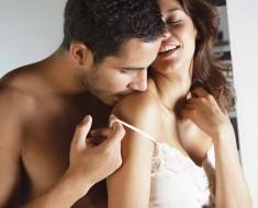 Hispanic man kissing girlfriend's shoulder
