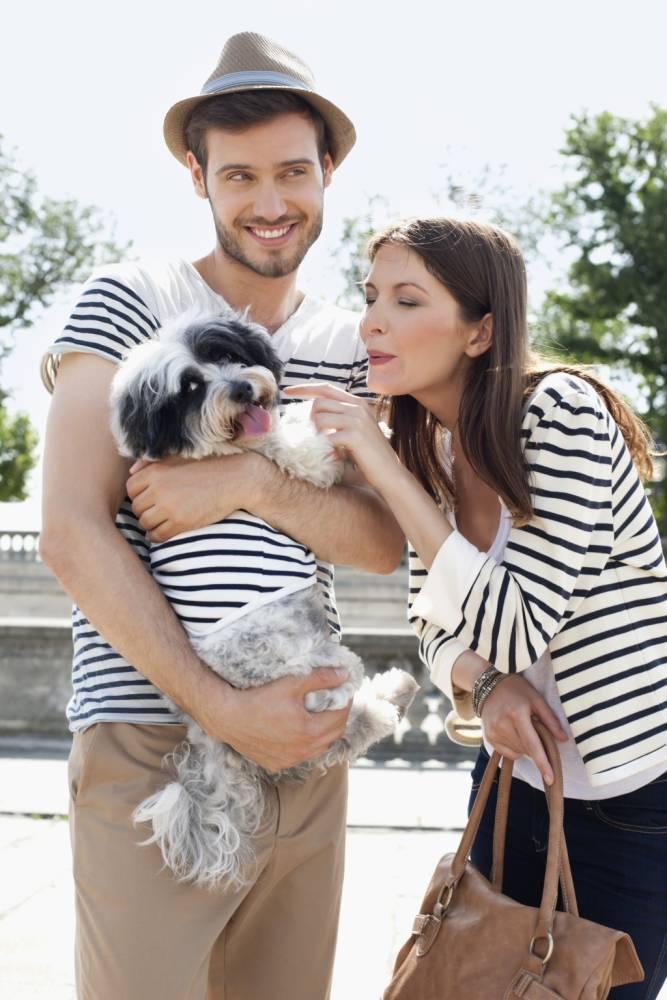 Woman loving with a puppy held by a man, Paris, Ile-de-France, France