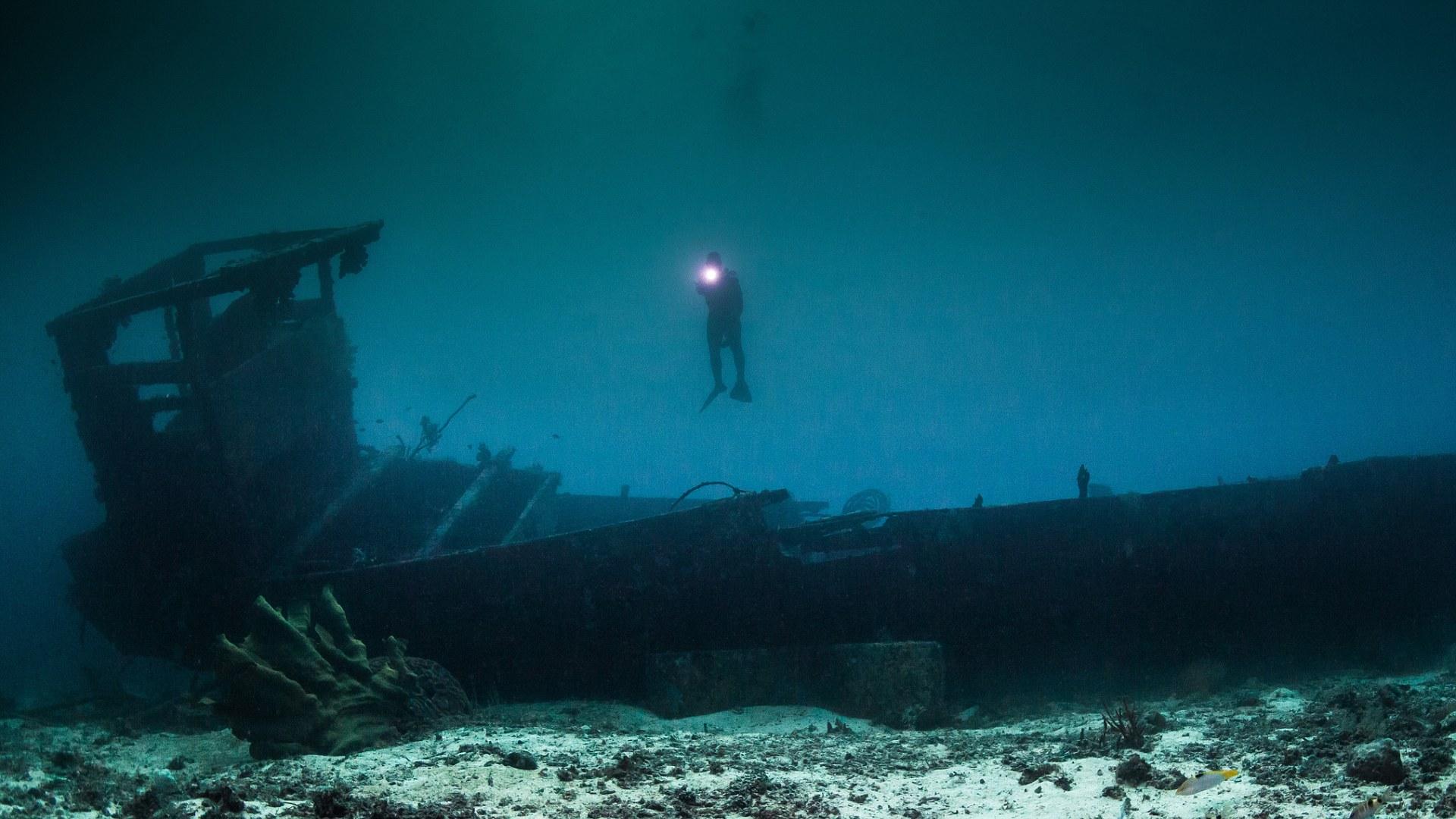 Scuba Diver Explores Wreck In Undersea