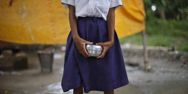 A school girl holds a container to receive free mid-day meal, distributed by a government-run primary school, at Brahimpur village in Chapra