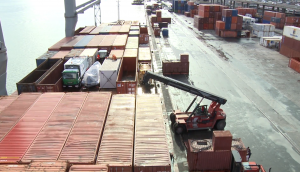 forklift-tractor-moving-metal-shipping-containers-in-harbor_h5v