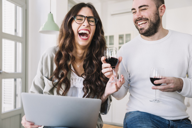 laughing-couple-with-wine-and-notebook_23-2147766982