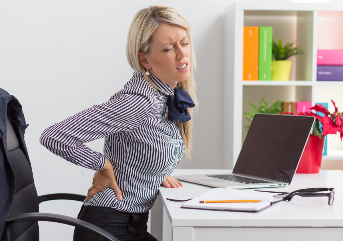 Woman having back pain while sitting at desk in office - Chiropractic Treatment Debunked